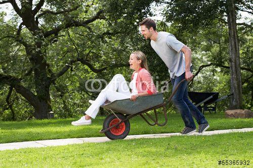 Man Pushing Woman In Wheelbarrow