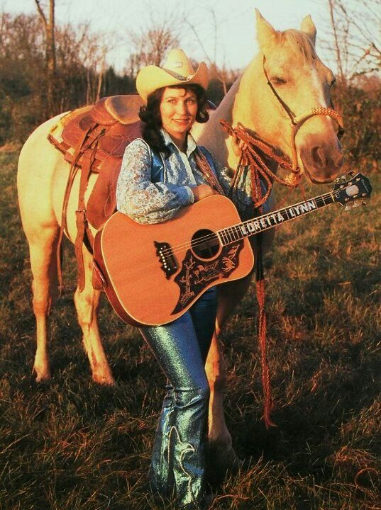 "Loretta Lynn with her golden brown acoustic guitar and her golden palomino in a portrait shot that reflects her song, ""If You're lookin at me, you're lookin at country"""