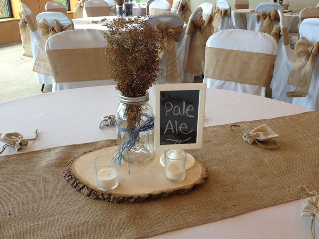 Rustic wedding with burlap chair sashes and burlap runners. Mason jar on sliced wood for centerpieces