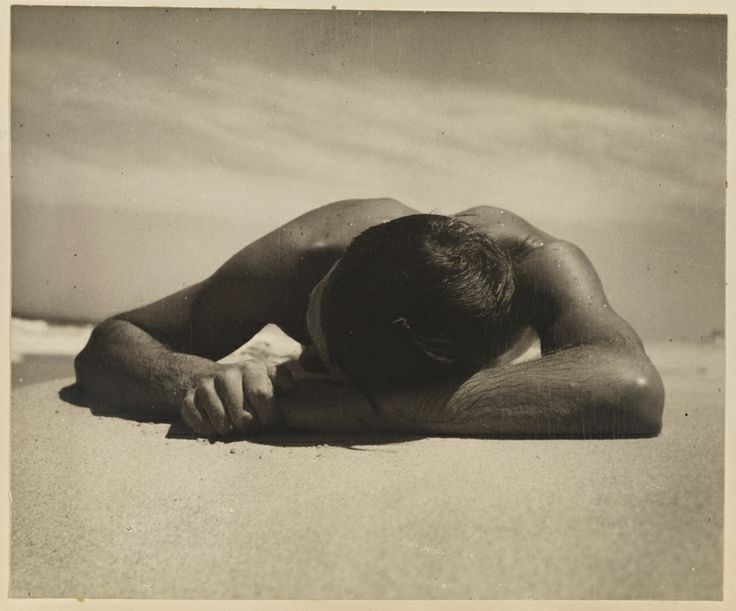 """Harold Salvage sunbaking, 1937. This was Max Dupain's preferred version of """"The Sunbaker"""" with his hands clasped. The better known version has his right hand extended in the sand. PXA 1951/19 http://www.acmssearch.sl.nsw.gov.au/search/itemDetailPaged.cgi?itemID=1036947"""