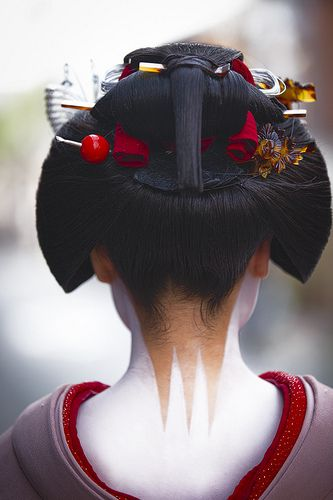 Maiko with exposed neck markings, red collar and elaborate hair decorations.