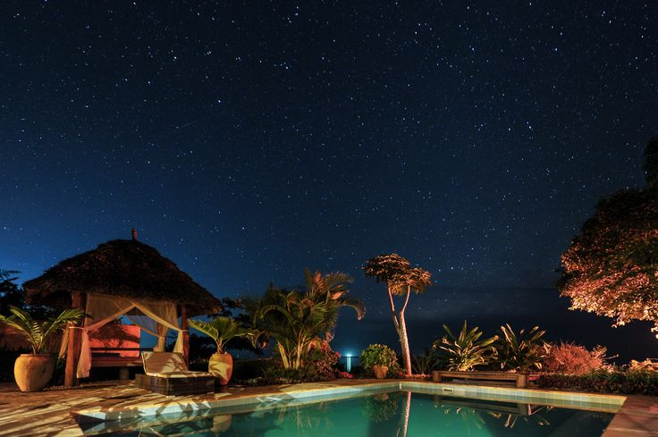 Garden with private pool and gazebo-style bed, under African sky. www.zanziresort.com