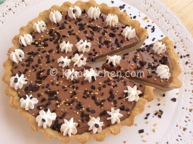 La crostata con crema al latte e nutella è un dolce goloso, da servire freddo e guarnire a piacere con glassa al cioccolato e panna montata.
