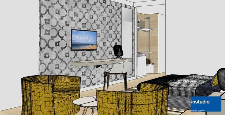 Ristrutturazione delle camere per Hotel vista mare. Superato l'ingresso, una boiserie in legno identifica l'area scrittoio, mentre un rivestimento murale con lo stesso decoro caratterizza il letto.