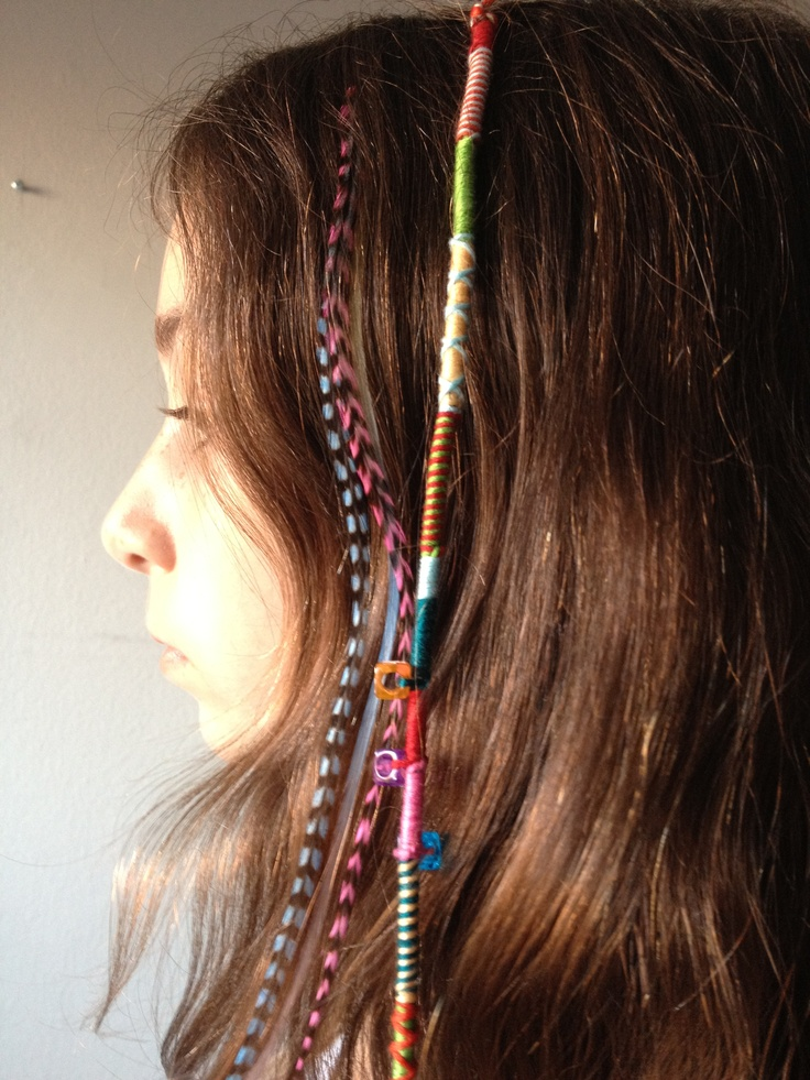 Hair wrap with friendship bracelet string, next to hair feathers.