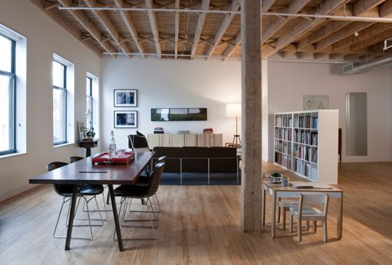 Industrial Loft retrofit in Williamsburg, Brooklyn features a Slot table designed by GSDO, Bertoia chairs, and framed photos by artist Matthew Baum on the walls.