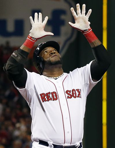 Boston Red Sox designated hitter David Ortiz raises his hands while crossing the plate with a two-run home run in the first inning of a base...