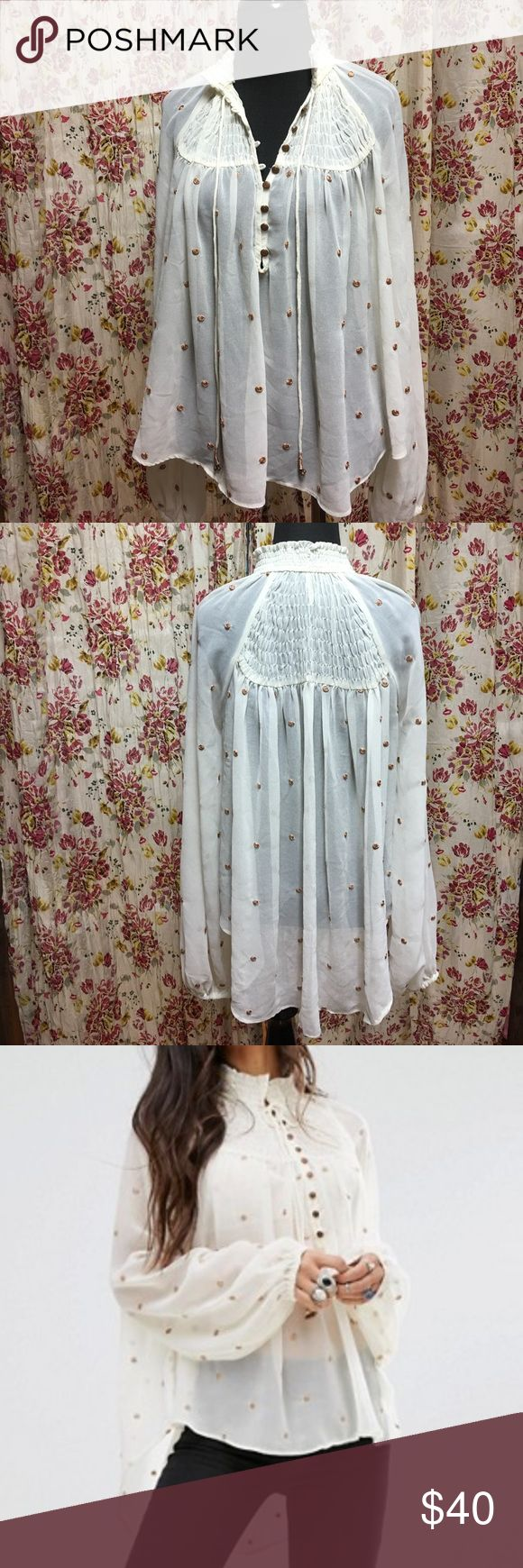 Free People Blouse Free People Ready To Run Smocked Blouse.  Sheer cream material.  Bronze embroidered metallic dots.  Smocked front and back.  Ruffled high neck.  Elastic cuffs.  Tie neck.  High low hem.  Excellent used condition. Free People Tops Blouses