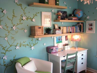 I like the green wall decal with the 3D white flowers on top of the teal walls. The white furniture and green accents rally pulls the corner together