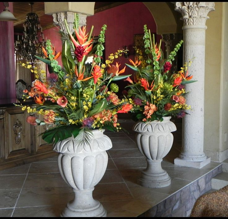 Large Artificial Tropical Flower Arrangements In Concrete Urns Add An Elegant Splash Of Color To The