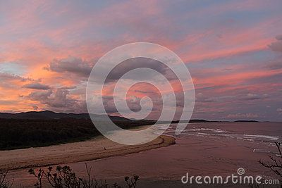 The pink sky of sunset where Boambee Creek meets the Pacific Ocean near Coffs Harbour, NSW