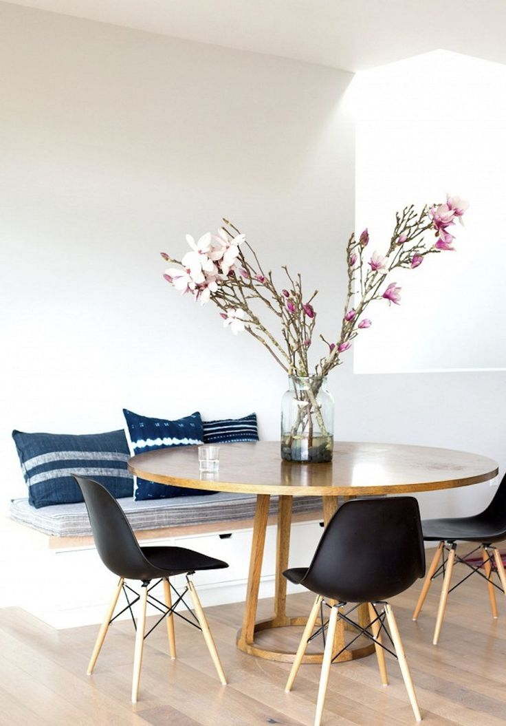 Sweet & simple: modern round dining table with mid-century chairs & banquet adorned with indigo cushions. Top 10 Modern Round Dining Tables ♥ Discover the season's newest designs and inspirations. Visit us at  www.moderndiningtables.net #diningtables #homedecorideas #diningroomideas @ModDiningTables