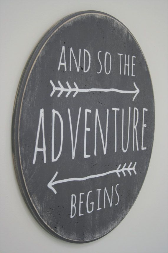 And so the adventure begins! This is a wood sign that measures 20 round. The background shown here is Dark Gray. Lettering is White.  This piece is hand painted and sanded for a distressed/rustic look. It is then sealed with a water based finish.  The back is left unfinished and comes ready to hang.