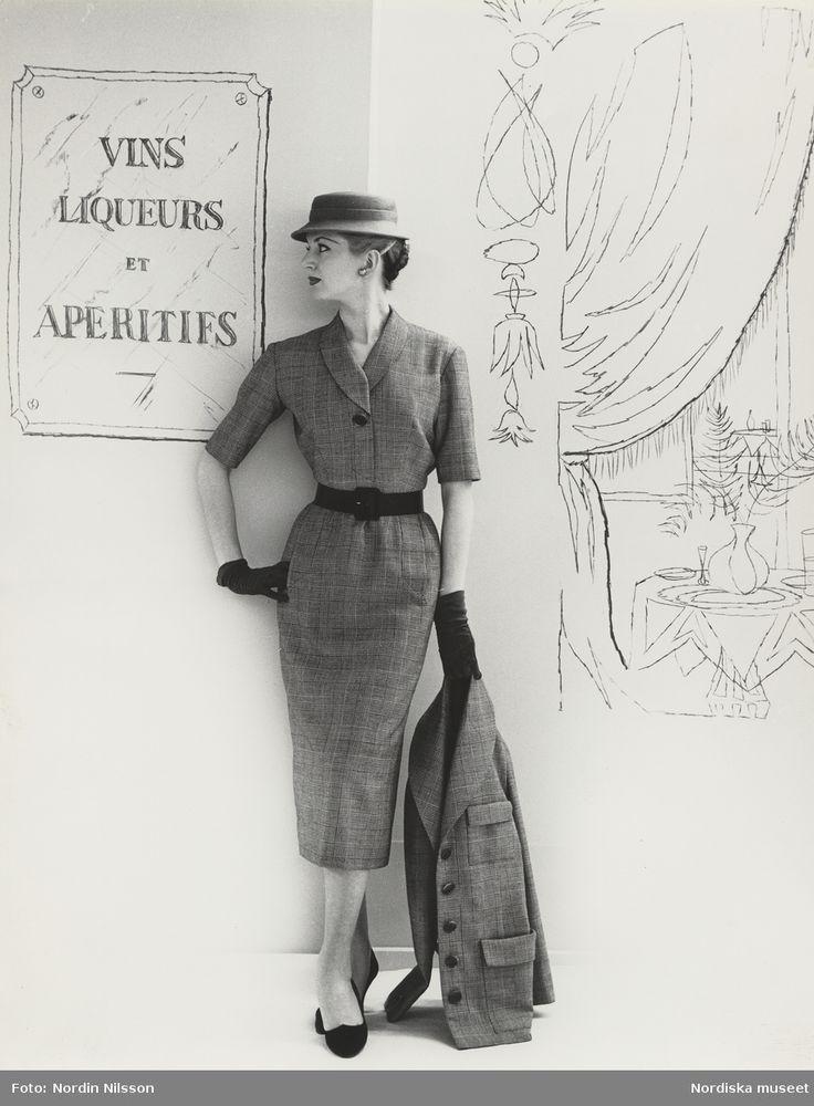 1955. Modell i klänning med skärp, hatt, handskar och kavaj i handen. Tecknad bakgrund. Foto: Nordin Nilsson
