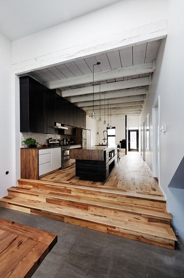 3 steps from dining room to living room:  concrete & wood floors. rough beam ceiling, industrial lighting