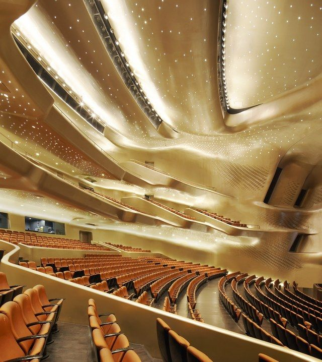 The Guangzhou Opera House in China's Guangdong province is shaped to resemble two pebbles on the bank of the Pearl River. The interior of the shimmering main auditorium is lined with panels of gypsum molded in flowing, organic shapes and lit with thousands of tiny lights that resemble stars in the night sky.