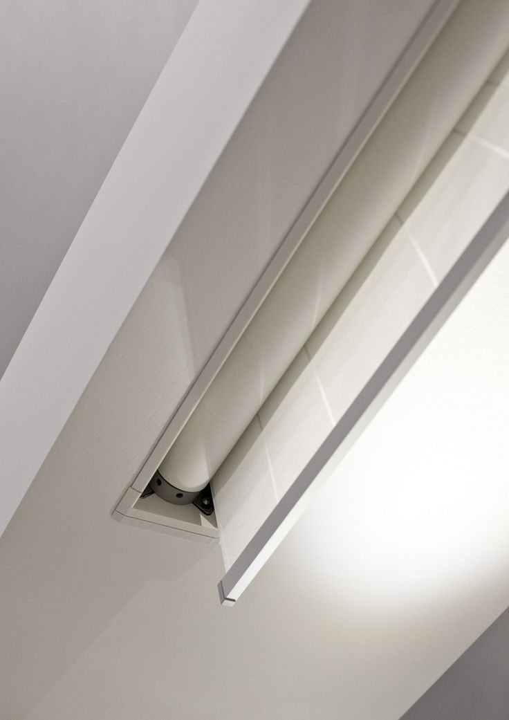 recessed roller blinds along western wall - hidden in soffit between upper windows and lift-and-slide doors.