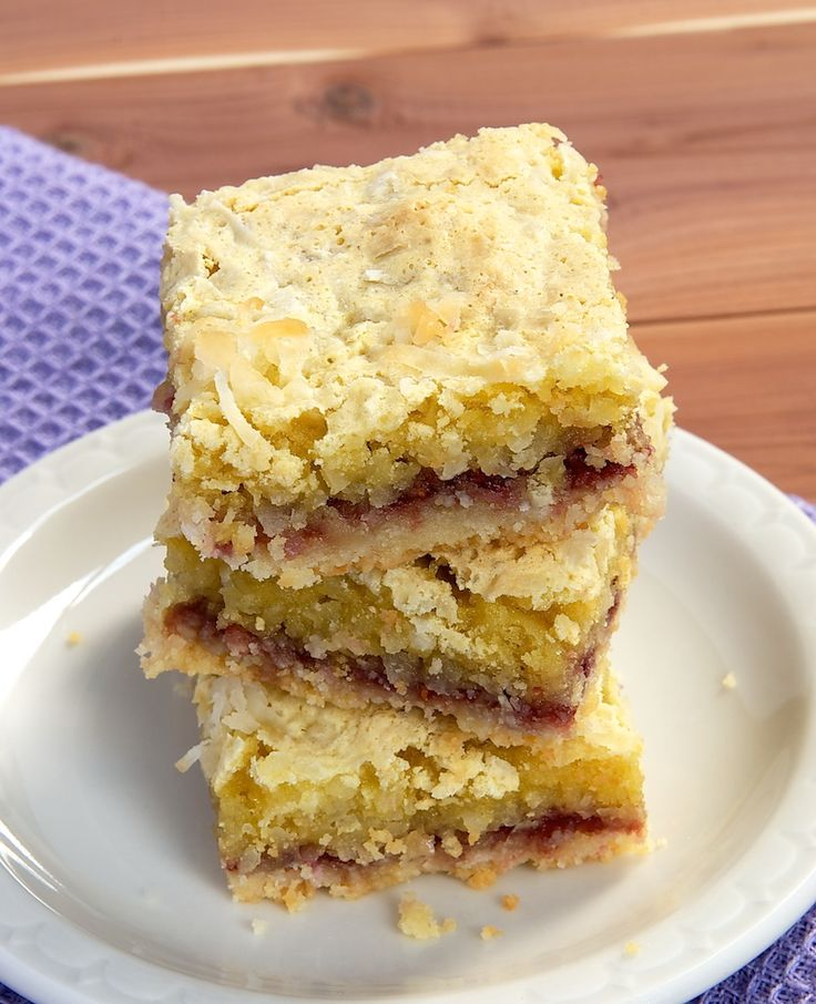 Coconut Raspberry Bars are a delicious dessert made up of an almond shortbread crust, raspberry preserves, and a gooey coconut topping.