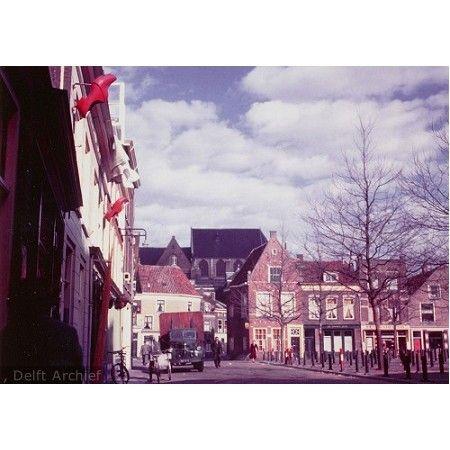 Delft,Beestenmarkt, 1956.  Fotograaf W.G. v/d Akker. De Beestenmarkt gezien naar het noorden richting Burgwal met aan de noordzijde de panden Beestenmarkt 2 - 8 en bebouwing aan de westzijde. Achter de vrachtwagen bebouwing aan de Burgwal met daarboven een gedeelte van de Nieuwe Kerk. Op de Beestenmarkt de karakteristieke paaltjes met swastika uiterlijk die in 1988 gedeeltelijk verwijderd zijn.