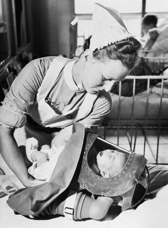 GAS DRILL AT A LONDON HOSPITAL: GAS MASKS FOR BABIES ARE TESTED, ENGLAND, 1940.   WWII