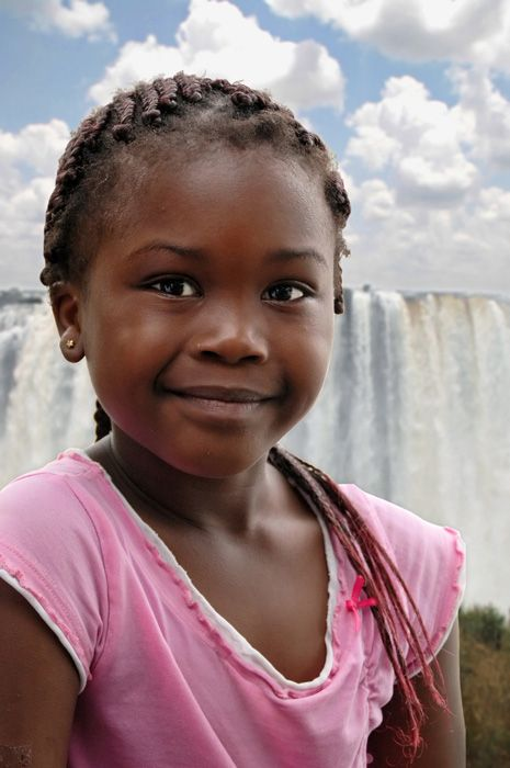 A girl poses in front of the mighty Victoria Falls, Zambia.  by dvlazar