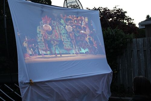 Our easy tutorial guide on how to host the perfect DIY backyard movie night with a DIY movie screen, seating, snacks and decor using your Springfree Trampoline.