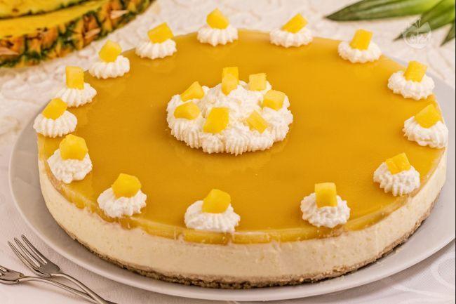 La cheesecake tropicale è una torta fresca e golosa composta da una crema di formaggio fresco e pezzi di ananas e mango, perfetta per l'estate.