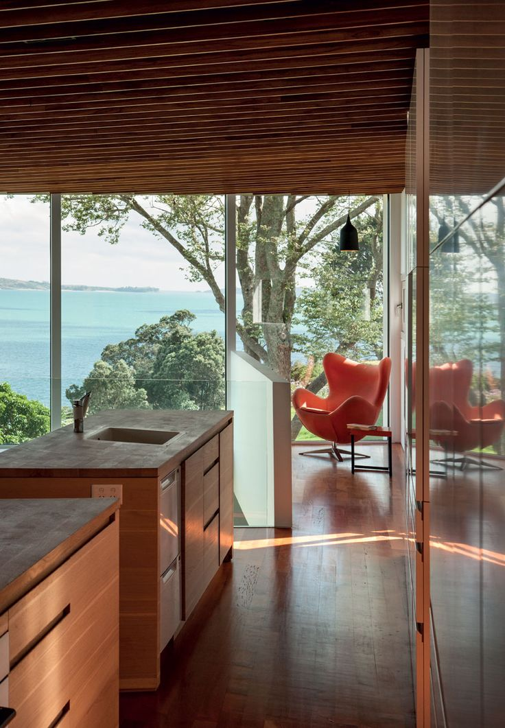 A quiet nook encourages quiet contemplation of the trees and water. The kitchen cabinetry was made from an oak tree felled on the site.