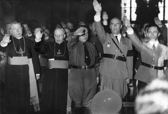 Nazi salutes in honor of Hitler. Catholic Bishops with  Joseph Goebbels (far right) and Wilhelm Frick (second from right).