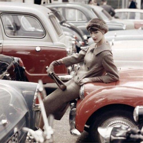 A model leans on a car for Vogue, 1955. Photo by Norman Parkinson.