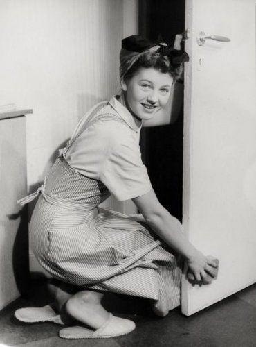 Huishouden, deuren lappen. Een huisvrouw met schort aan en doek om haar hoofd.