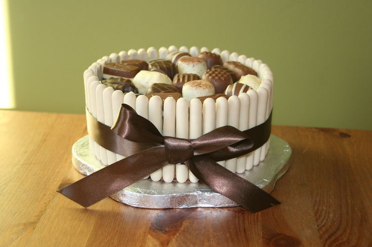 Devils food cake with chocolate buttercream. White chocolate fingers around the outside and chocolates on the top.
