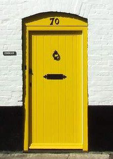 Yellow front door is perfect with the painted brick.