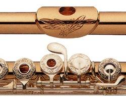 I can only dream, because this is worth tens of thousands of dollars… [Gold flute with engraved mouthpiece and keys]