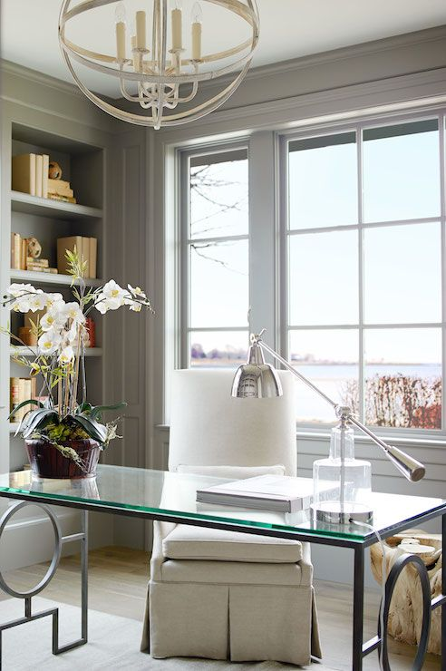 Chic home office features a silver sphere chandelier illuminating a glass-top desk with geometric base paired with a linen skirted chair