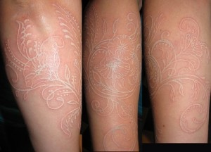 white henna looking tattoo on inside of foot arch