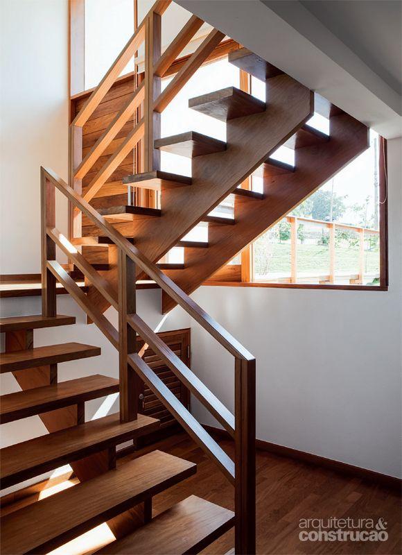 Casa incorpora árvore no deck e se beneficia de sua sombra_A circulação acontece na área do hall, que tem escadas de perobinha.