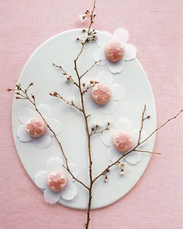 Sweet mochi treats placed on cherry-blossom confetti along a flowering branch