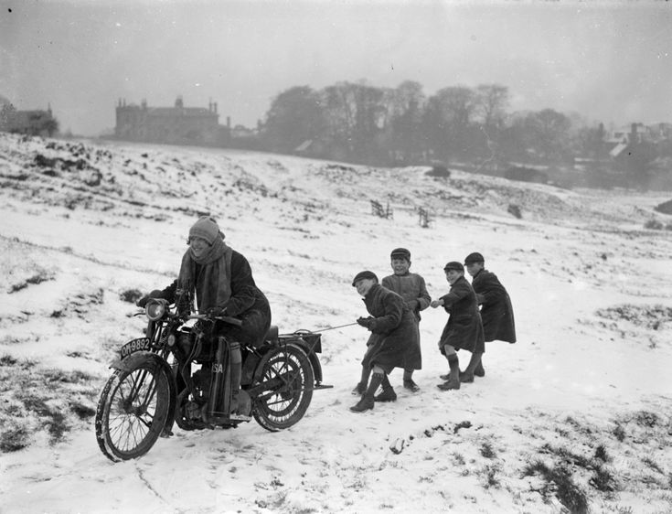 """This looks like a blast!  Children being pulled along by a woman on a motorbike in London, 1926 in the snow.  Most likely Nancy Debenham... who wrote the book """"Motor-Cycling for Women"""" with her sister."""