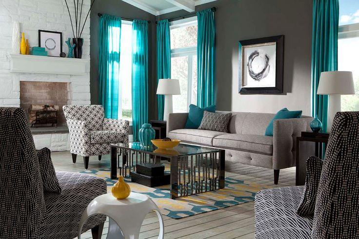 Бирюзовые шторы и серая мягкая мебель.