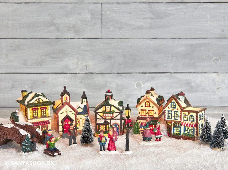 Flot juleby i porcelæn med 15 dele og lys. Julebyen indeholder 5 huse i gammeldags stil og du finder bl.a. butikker og en kirke. Derudover en fin bro, en lygtepæl, 4 figurer med personer på og 4 træer. Den medfølgende LED lyskæde er ret smart med en stor pære til hvert hus.