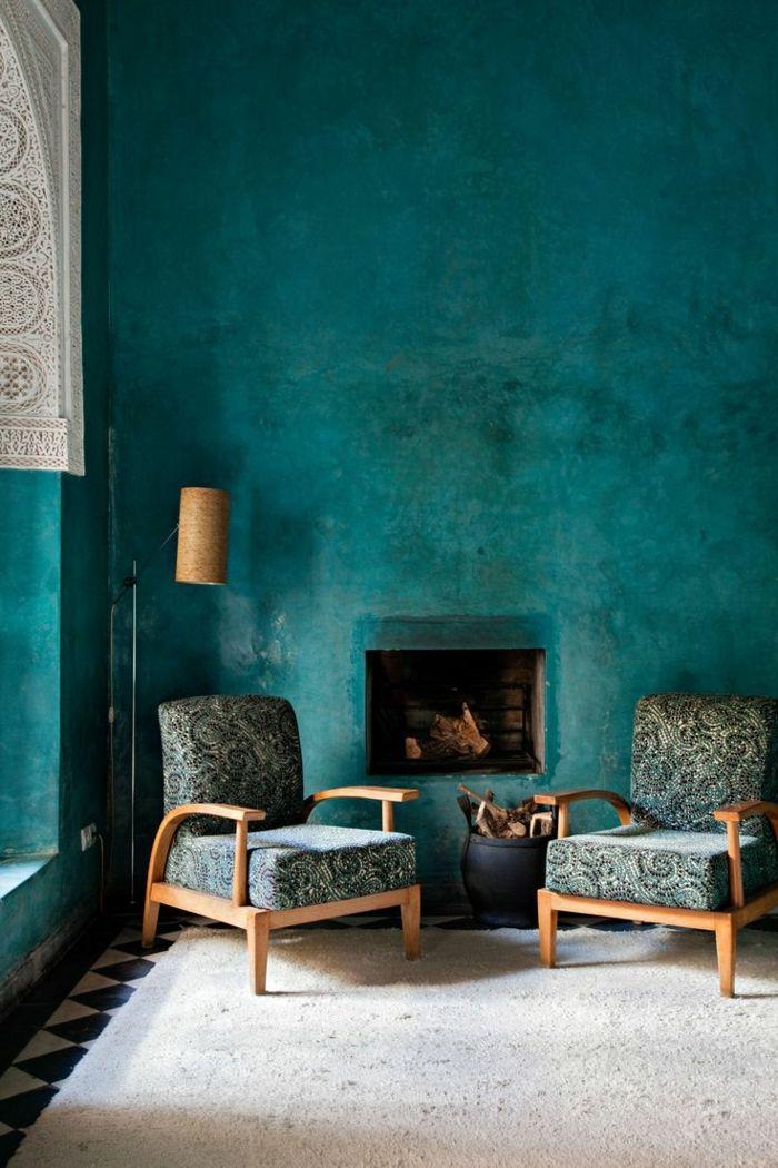 wandfarbe petrol wohnzimmer minimalistisch kamin sessel sitzecke