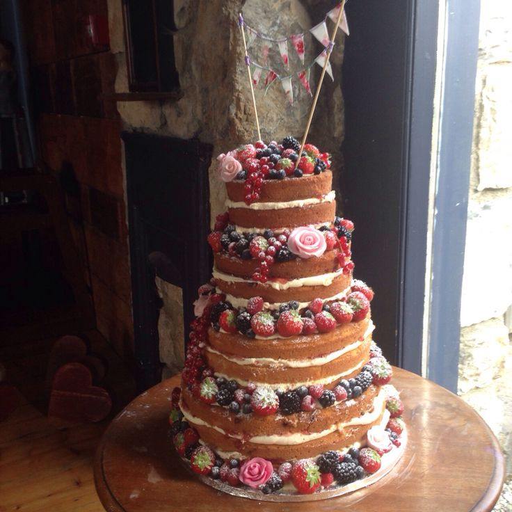 4 tier naked cake dressed with fresh berries and pink fondant roses, topped with hand made bunting. www.kellylou.com