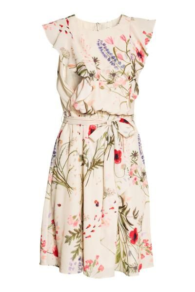Nursing dress in an airy, patterned weave with  short, frilled sleeves. Elasticated seam at the waist, detachable tie belt and gently flared skirt. The dres