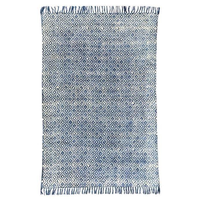 Tapis en coton indigo tissé main Tikola Une très belle fabrication artisanale : letapis Tikola est tissé à la main sur des métiers traditionnels en bois dans le Nord de l'Inde. Chaque pièce est donc unique et les dimensions peuvent du coup varier de quelques centimètre par rapport au format indiqué