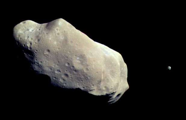 """Asteroid Ida and its satellite Dactyl. Image made from data collected by the spacecraft Galileo on its close approach to the asteroid (1993-08-28). Mona Evans, """"Astronomy April Fools"""" http://www.bellaonline.com/articles/art183019.asp"""