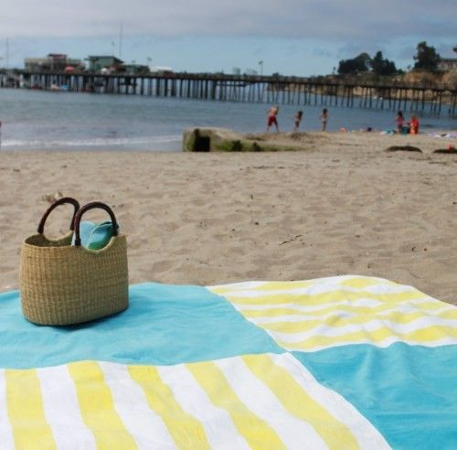Use old towels to make this huge beach blanket.  Add a vinyl tablecloth to the back: blocks sand, doubles as tablecloth.  cool.