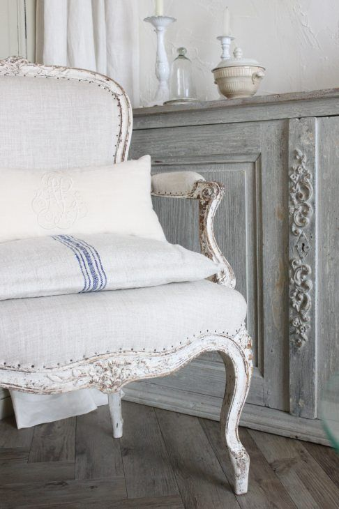Lovely faded blue sideboard and linens in a white chair.