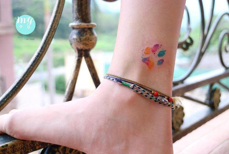 Tiny watercolour Dog's paw footprint tattoo