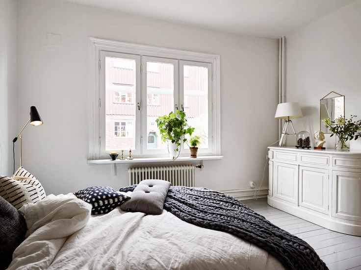 A Swedish apartment with a cosy bed and glossy grey floor. Stadshem.
